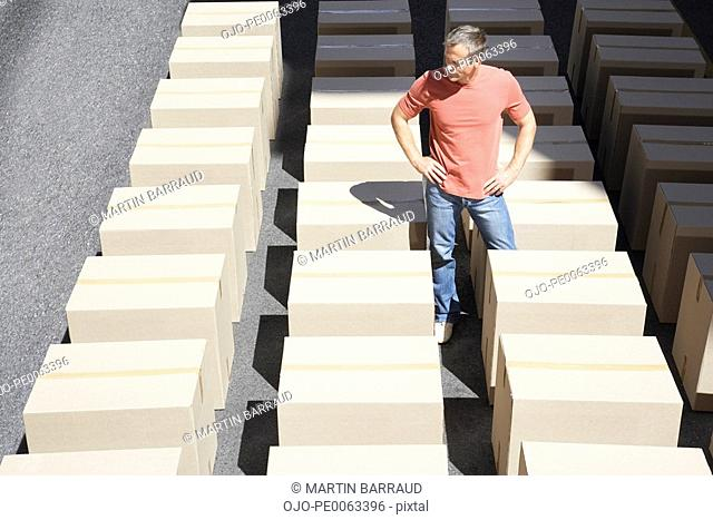 Man standing in the middle of rows of boxes