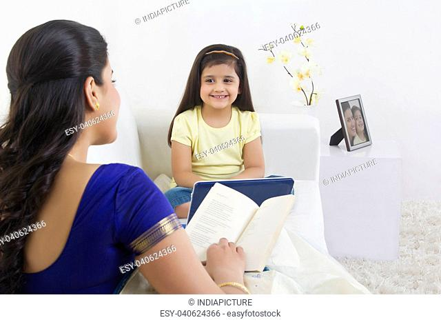 Mother with book and daughter with computer