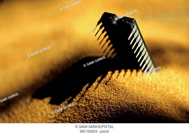 Computer chip half-buried in sand