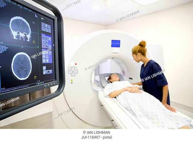 Hospital Radiographer With Female Patient Operating CT Scanner