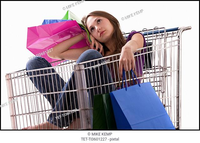 Bored woman sitting in a shopping cart with her purchases