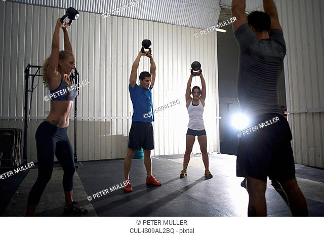 People working out with kettlebell in group class