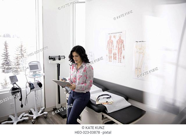 Female doctor noting on medical chart in clinic examination room