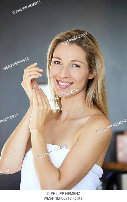 Portrait of smiling blond woman applying face cream in the morning