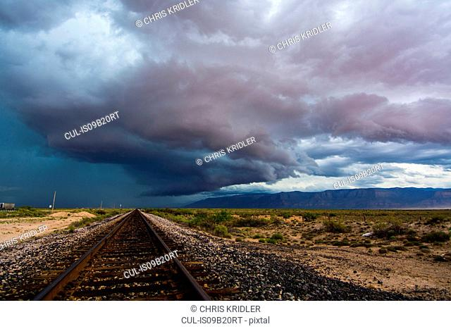Storms moving over plains into the mountains, as seen over railroad tracks near Alamogordo, New Mexico