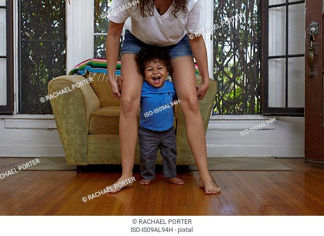 Male toddler taking first steps with mother in sitting room