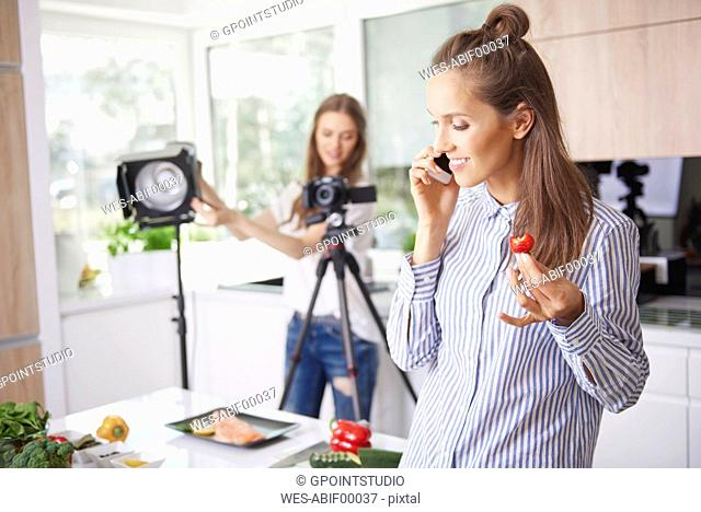 Woman talking on the phone and eating strawberry