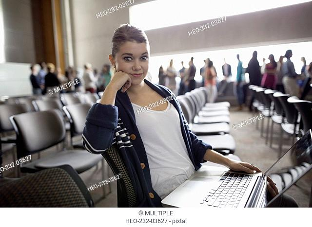 Portrait confident student with laptop in auditorium