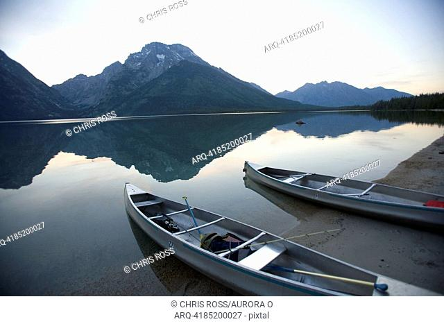 Two canoes at dusk are beached on the shore of Lake Leigh with the Grand Tetons in the distance