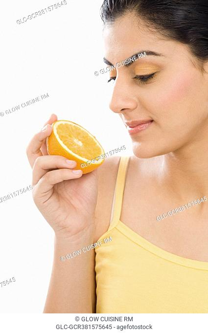 Close-up of a woman holding a half of orange