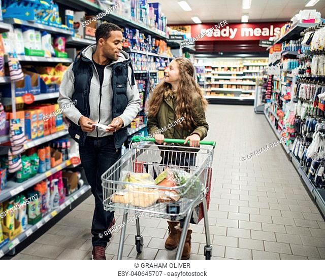 Little girl and her father are walking down an aisle at the supermarket with a trolley and a shopping list