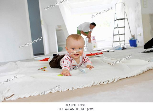 Baby crawling on rug in new home