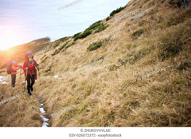 Two girls with backpacks walk along a trail in the mountains
