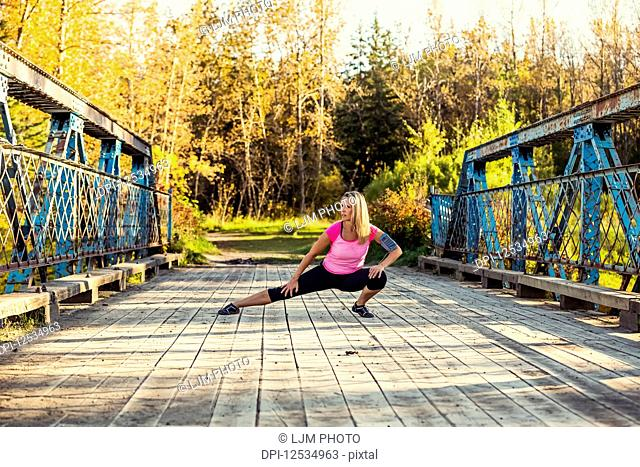 An attractive middle-aged woman pauses to stretch out her legs on a bridge during a run on a beautiful warm fall evening in a city park; Edmonton, Alberta