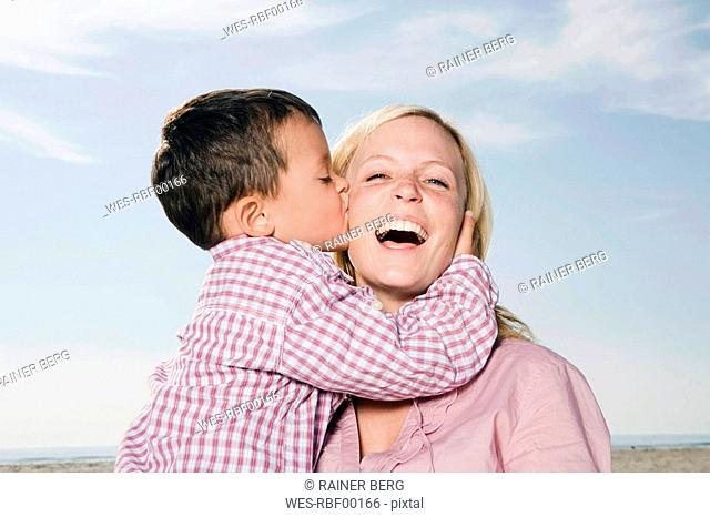 Germany, Schleswig Holstein, Amrum, Son 3-4 kissing mother, laughing, portrait