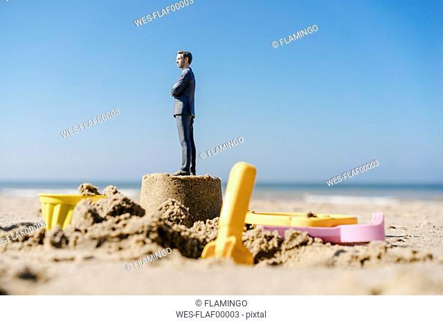 Businessman figurine standing on sand with toys around