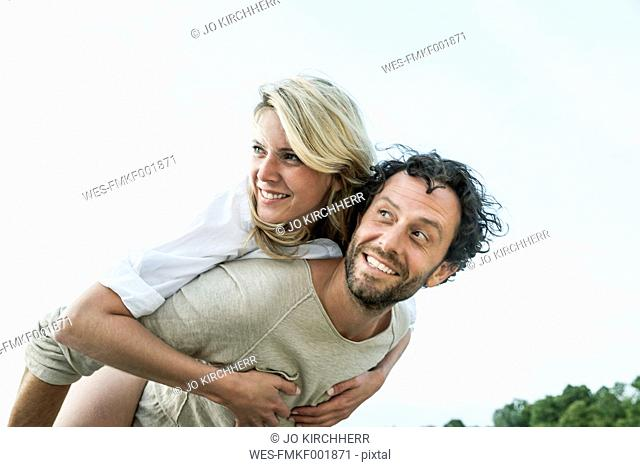 Smiling man carrying woman piggyback