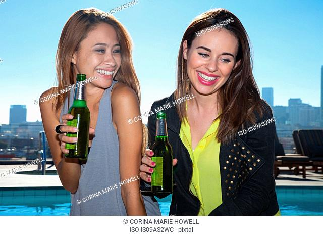 Two young adult female friends drinking beers at rooftop bar with Los Angeles skyline, USA