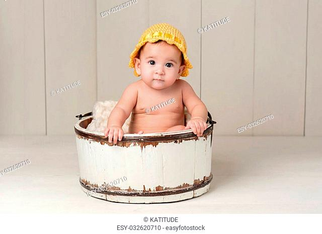 A 6 month old baby girl wearing a yellow knitted hat and sitting in a vintage wooden bucket. Shot in the studio on white hardwood floors and a white wooden...