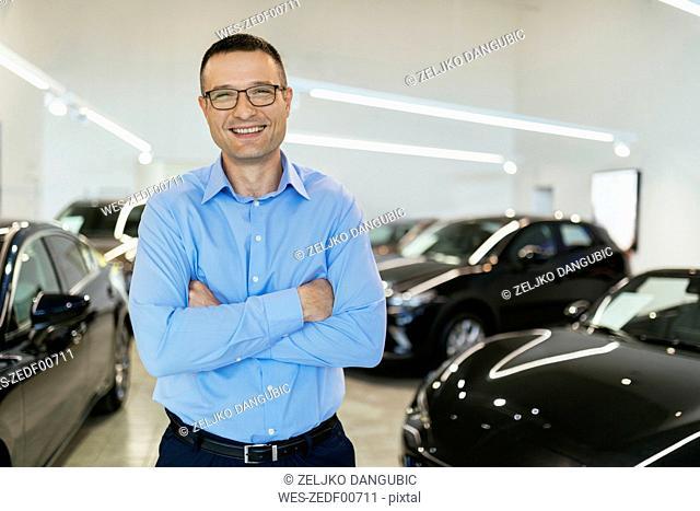 Car dealer standing in his shop