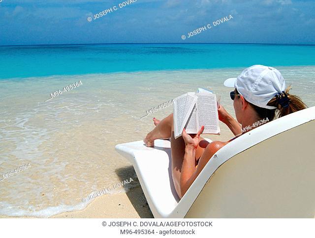 Woman reading book on tropical beach. Bikini Atoll. Marshall Islands