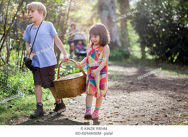 Young boy and girl carrying picnic basket
