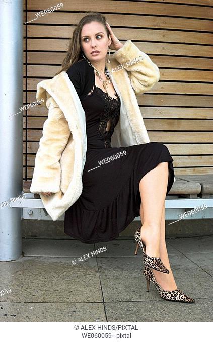 Young female fashion model wearing a fur coat