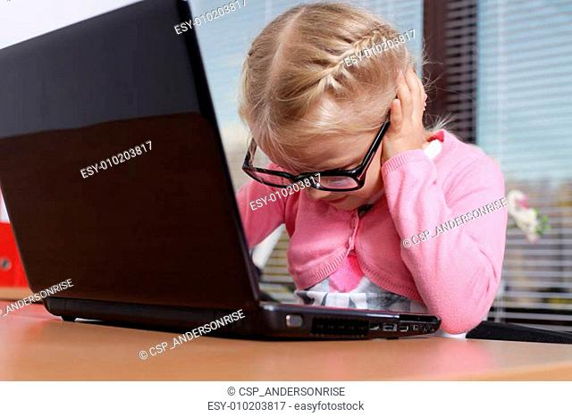 little girl with laptop in office