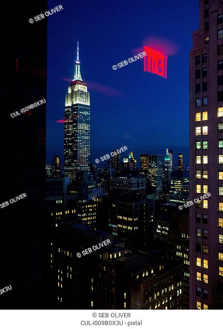 View through window of empire state building illuminated at night, New York, USA