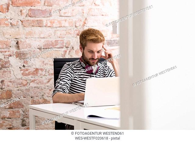 Young man using laptop at desk