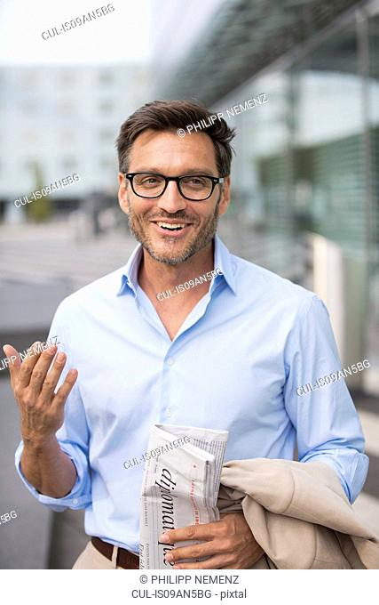 Mature businessman in city carrying newspaper and jacket