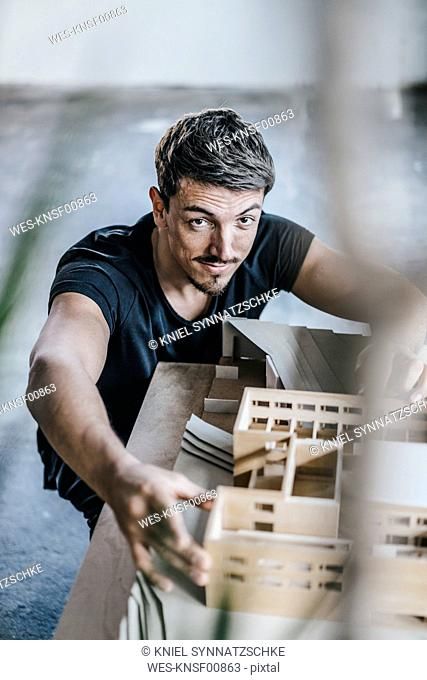 Portrait of confident architect working on architectural model