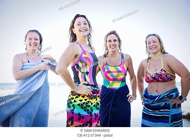 Portrait smiling, confident female open water swimmers drying off with towels