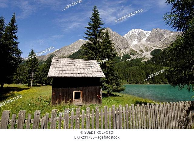 Cabin and wooden fence at the Antholzer lake in idyllic mountain scenery in the sunlight, Val Pusteria, South Tyrol, Italy, Europe