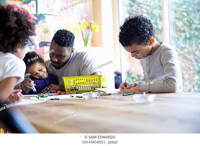 Father and children coloring at table