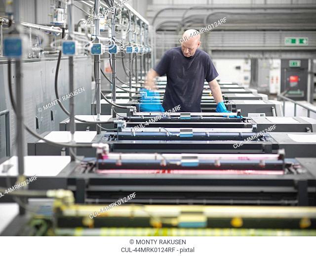 Printer inking printing press in shop