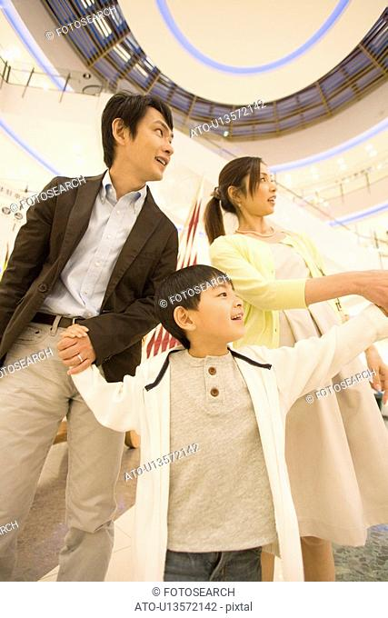Son and Two Parent Shopping in Department Store