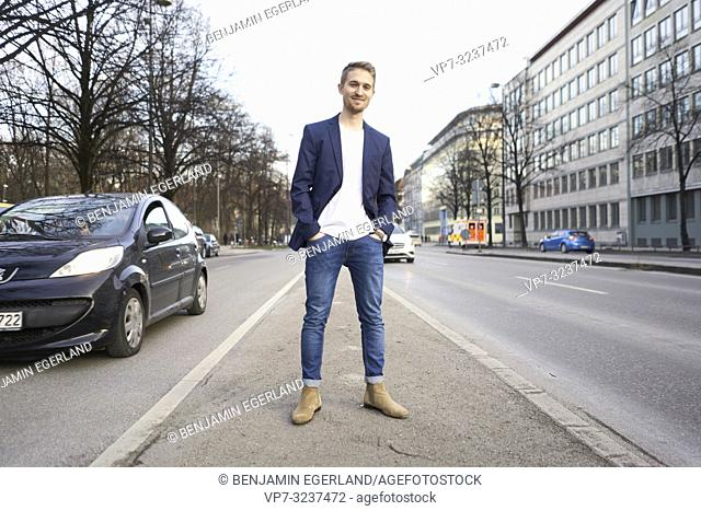 content man standing in middle of street in city, wearing business blazer combined with casual jeans, in Munich, Germany