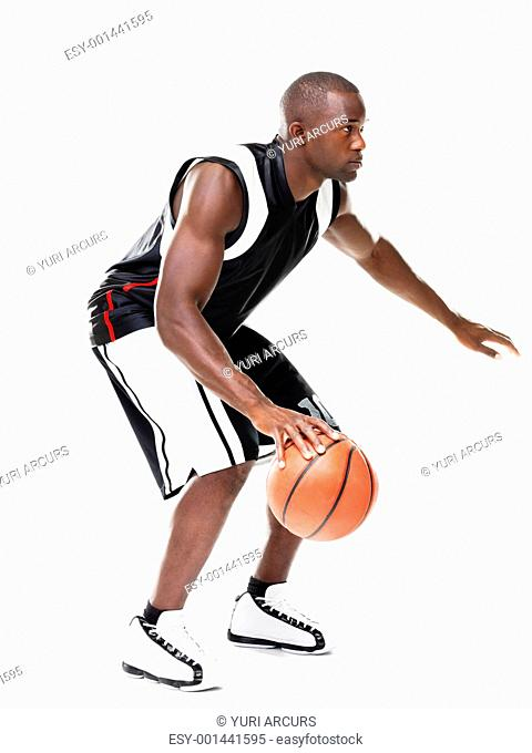 Portrait of a young african american male basketball player in action against white background