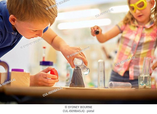 Primary schoolboy and girl doing test tube experiment in classroom