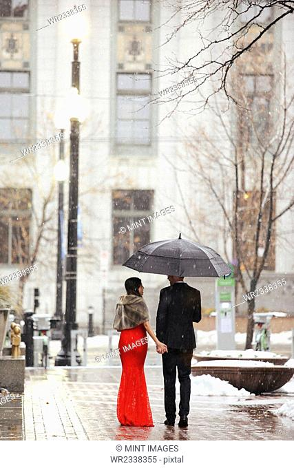 A woman in a long red evening dress with fishtail skirt and a fur stole, and a man in a suit, walking through snow in the city