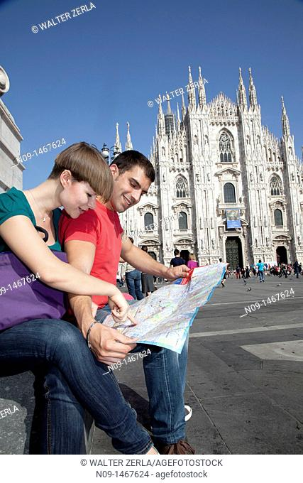 Young couple browsing a map in milan