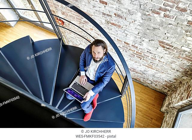 Businessman using laptop on spiral staircase