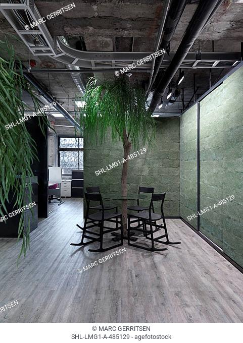 Modern circular table with tree in center in industrial office building