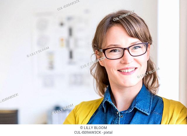 Portrait of young woman wearing eye glasses looking at camera smiling