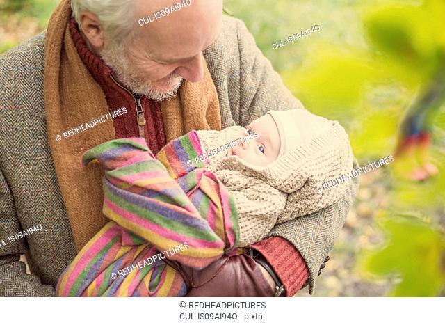 Grandfather cradling grandson, high angle