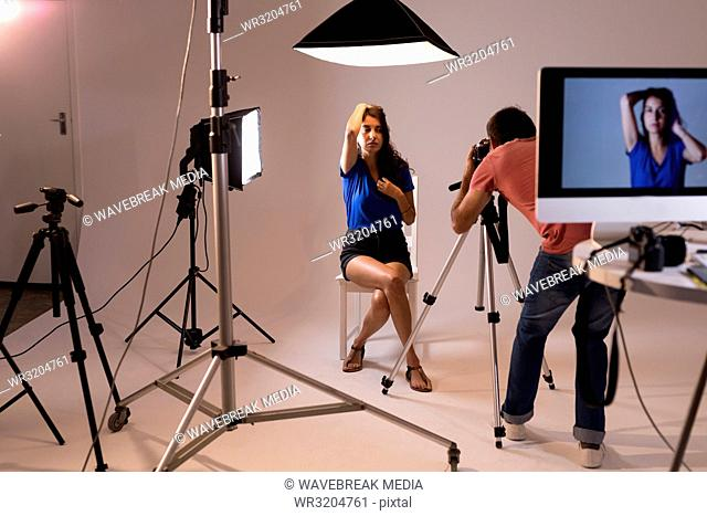 Male photographer clicking photos of model