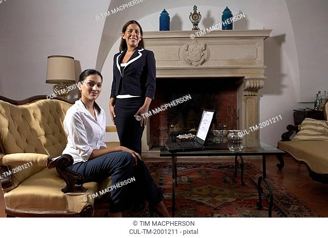 Two women with laptop in living room, smiling, portrait