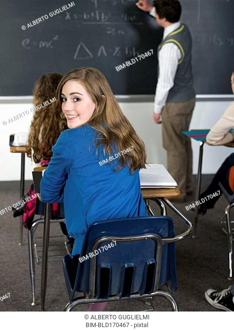 Student looking over her shoulder at desk in classroom