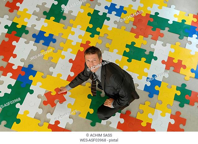 Businessman standing on jigsaw puzzle, holding piece of puzzle, smiling, portrait, elevated view